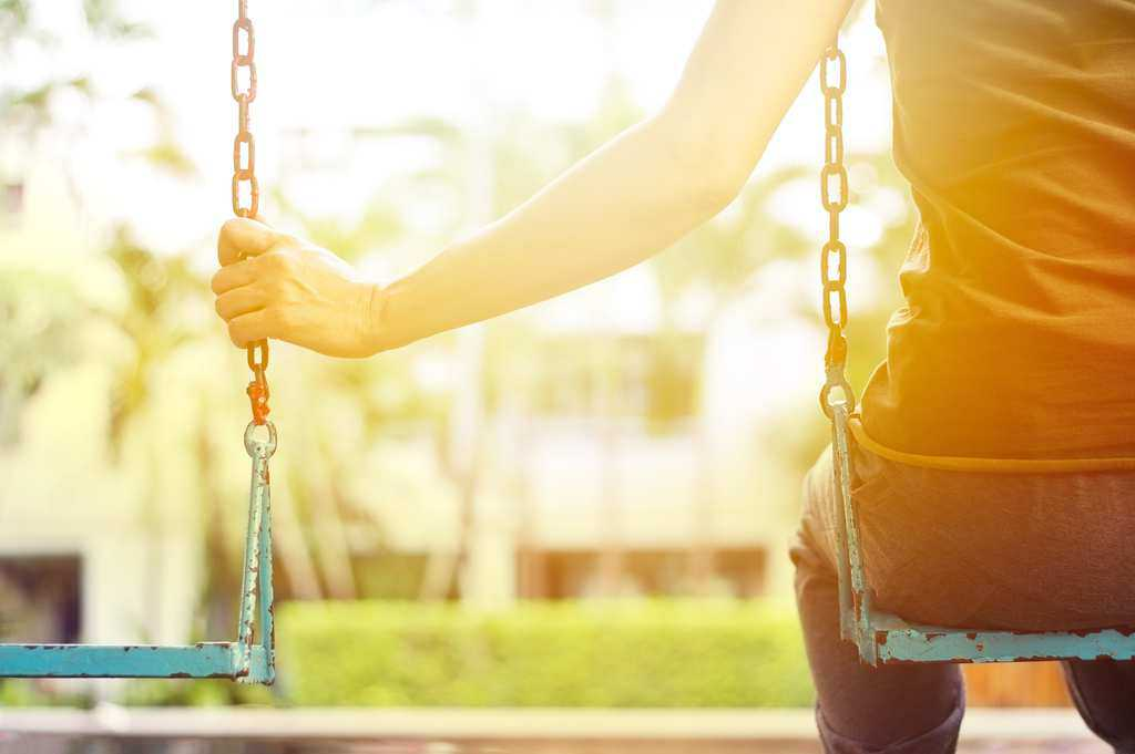 lonely woman sits on swing while holding on to empty swing next to her