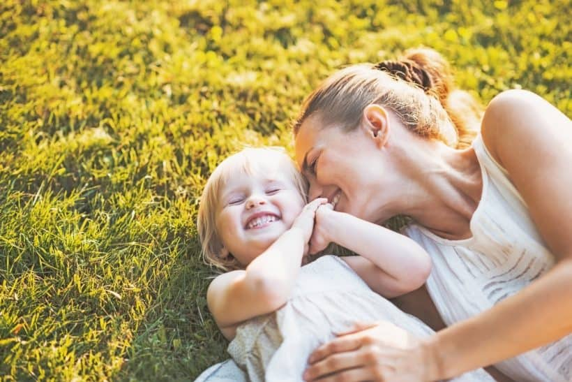 A mother and toddler laying in the grass while laughing.