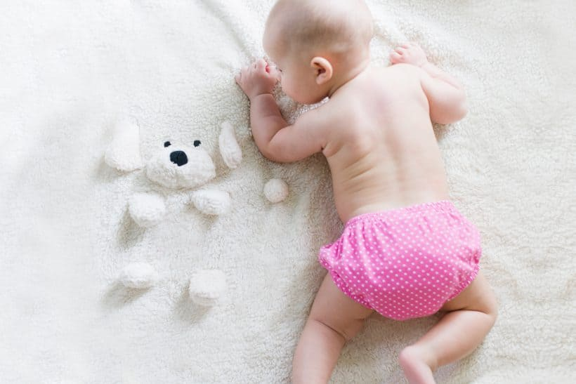 cute baby laying on blanket getting ready for sleep with a clean diaper