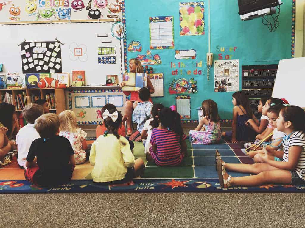 picture of kindergarten kids sitting in a circle listening to the teacher at school