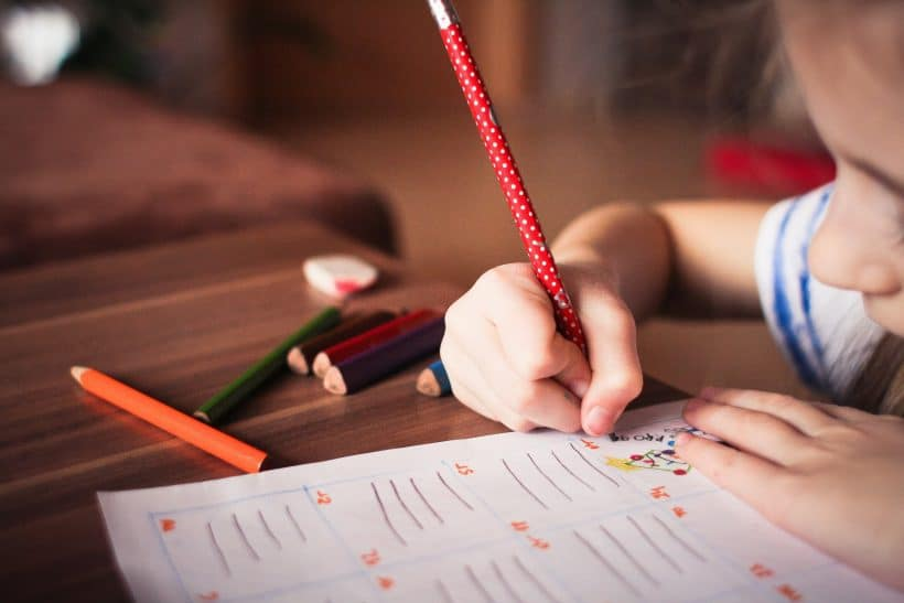 picture of child getting ready for back to school by drawing on a paper with a pencil