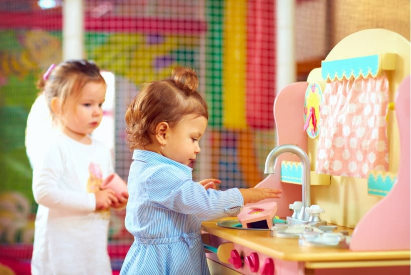 little toddler playing with the best play kitchen set