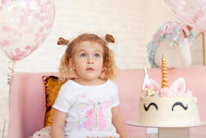 three year old girl getting peppa pig gifts for her birthday